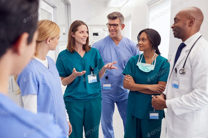 Multi-Cultural Medical Team Having Meeting In Hospital Corridor
