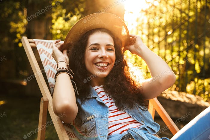 Photo of beautiful young brunette woman 18-20 wearing straw hat,