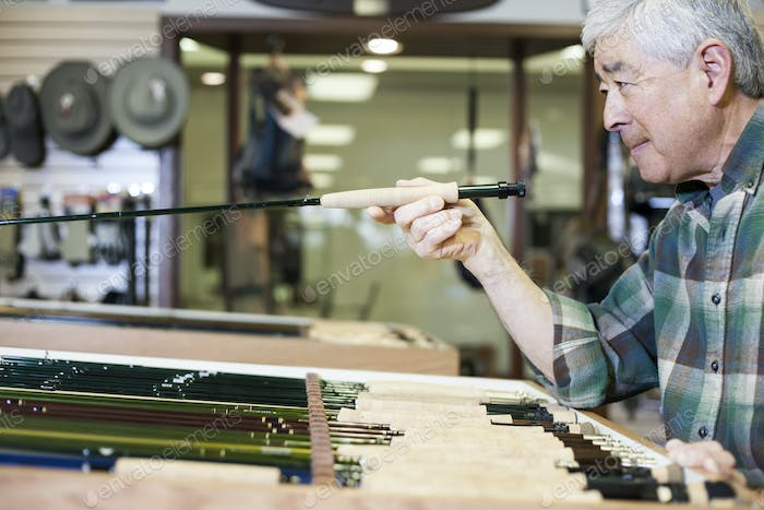 Asian American senior male checking the balance on a 5 weight fly fishing rod