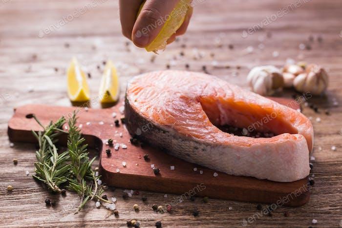 Японская или восточная кухня, Морепродукты, шеф-повар наливая лимонный сок замерзает в движении на стейк