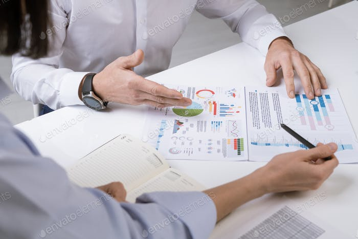 Hands of two financial managers over documents during discussion