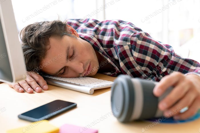Front view of tired Caucasian male graphic designer sleeping on desk in a modern office