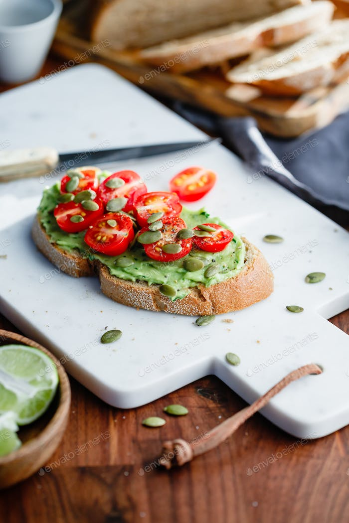 Avocado toast with cherry tomatoes and pepitas