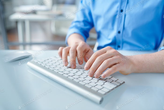 Creative designer in blue shirt touching buttons of computer keypad