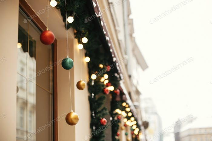 Stylish christmas fir branches with golden lights and colorful festive baubles
