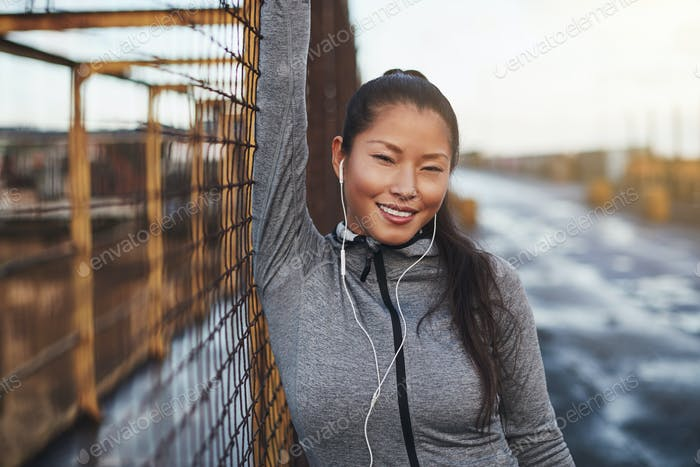 Sporty young Asian woman leaning against a mesh wall outside
