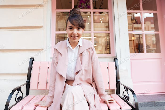 Smiling cute girl in pink jacket sitting on the bench