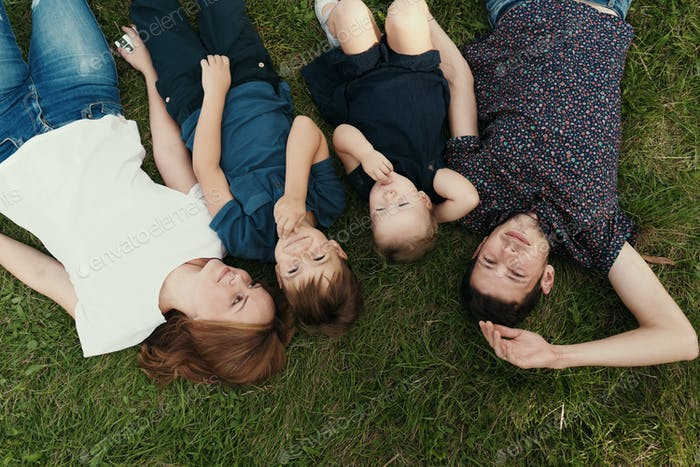 Portrait family with kids lying on the grass