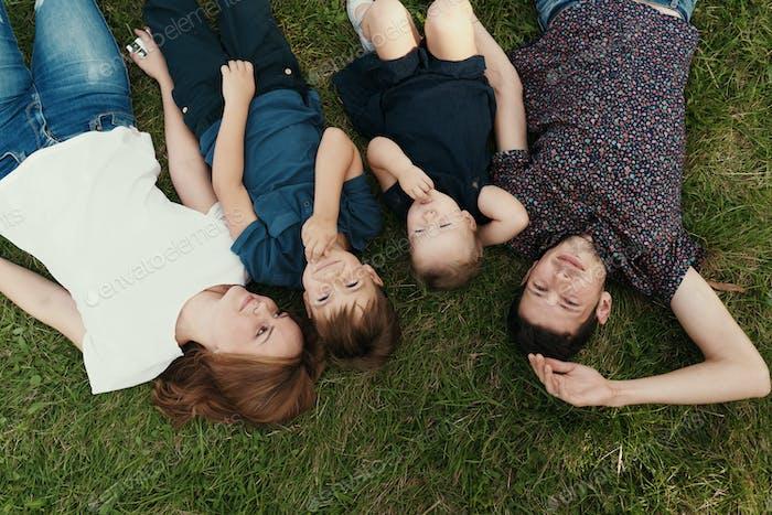 Porträt Familie mit Kindern auf dem Gras liegend