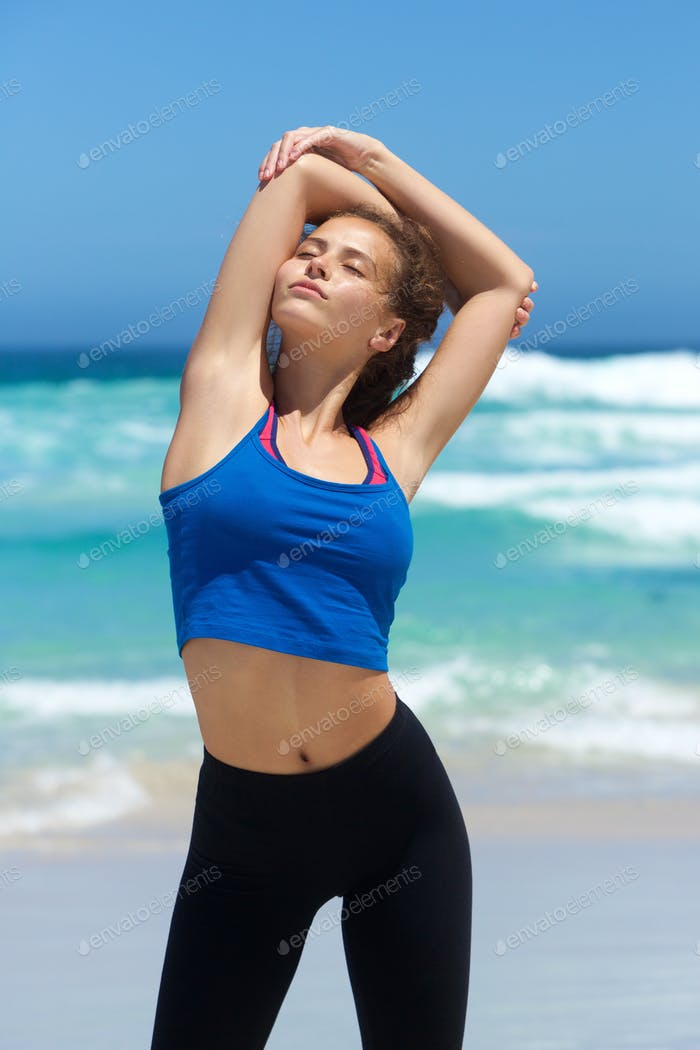 Beautiful young sporty woman stretching at the beach