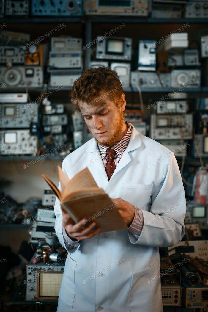Strange male scientist reading book in laboratory