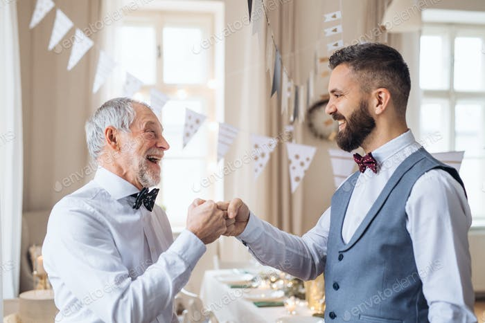 A senior and mature man standing indoors in a room set for a party, making fist bump.