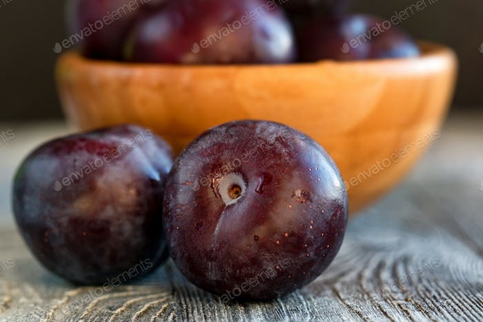 Garden plums in bowl on wooden table