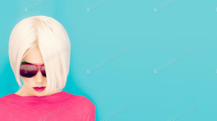 Fashion blond model with trendy haircut and sunglasses on blue b