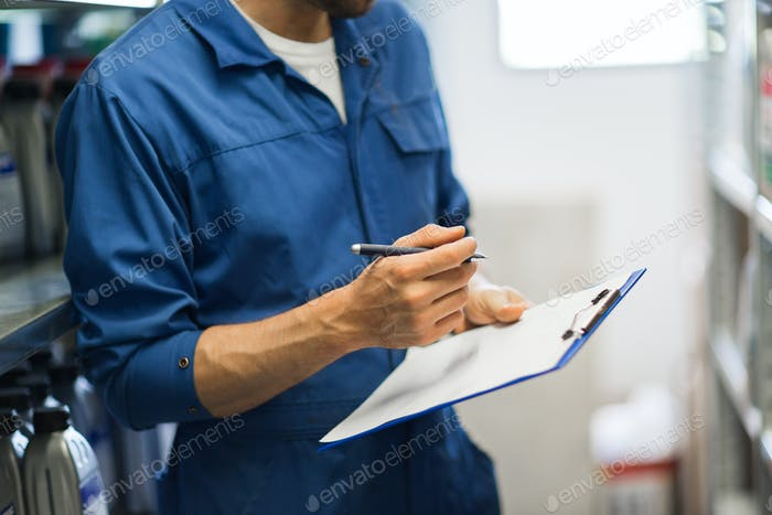 auto mechanic with clipboard at car workshop