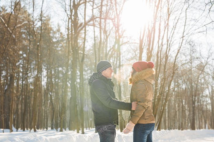 Young couple in love in winter forest