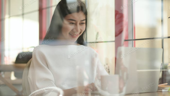 Young girl uses a laptop for video conference in a cafe, Shot from the outside through the glass.
