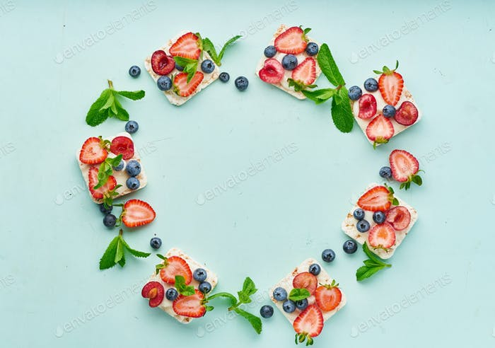 Rise crispbread frame with berries and fruits colorful concept on turquoise aquamarine