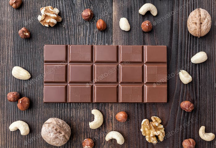 Delicious milk chocolate on wooden background