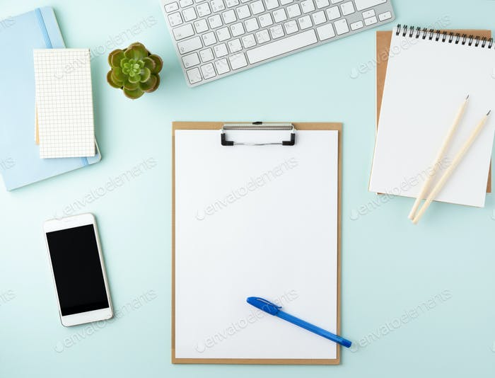 Top view of modern blue office desktop with blank notepad, computer, smartphone. Mock up,