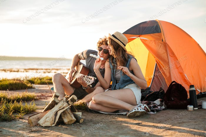 Couple playing guitar and eating fryed marshmallows near touristic tent