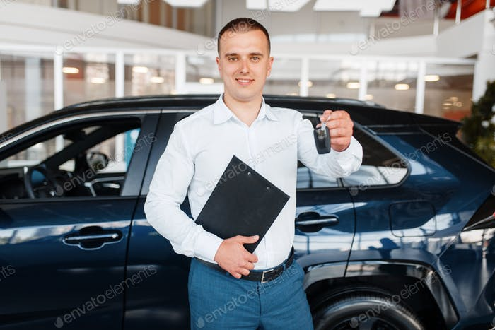 Salesman gives key to the new car in showroom