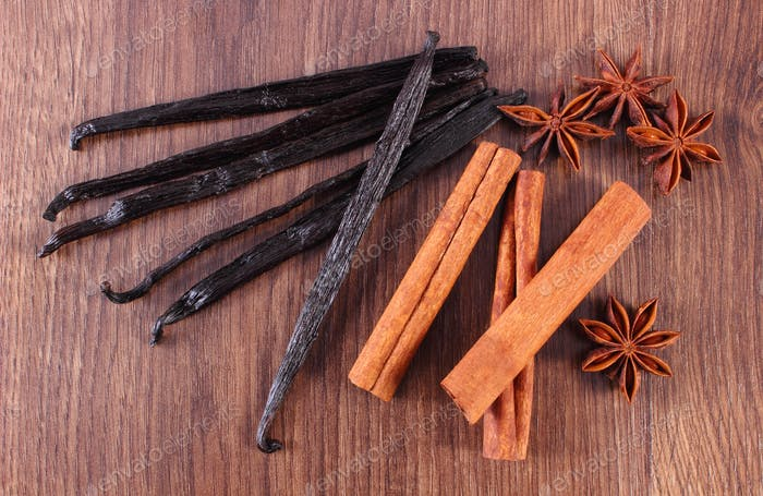 Fragrant vanilla, star anise and cinnamon sticks on wooden surface plank