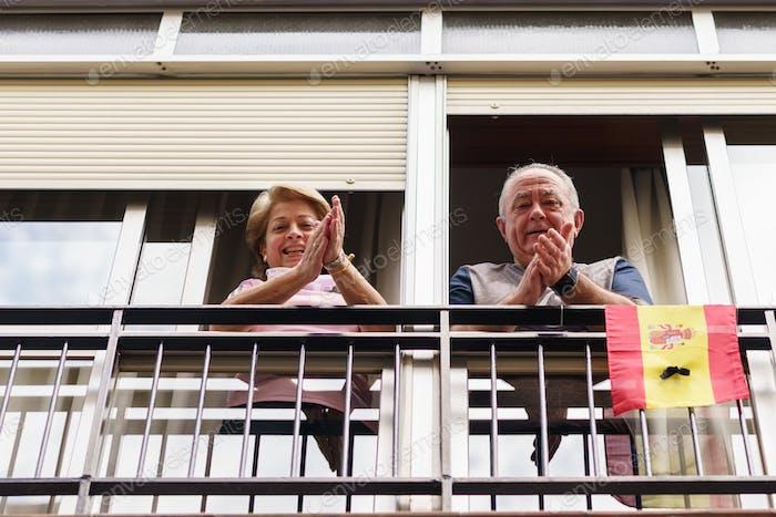 Älteres Paar klatscht in das Fenster zur Unterstützung von Menschen gegen das Coronavirus