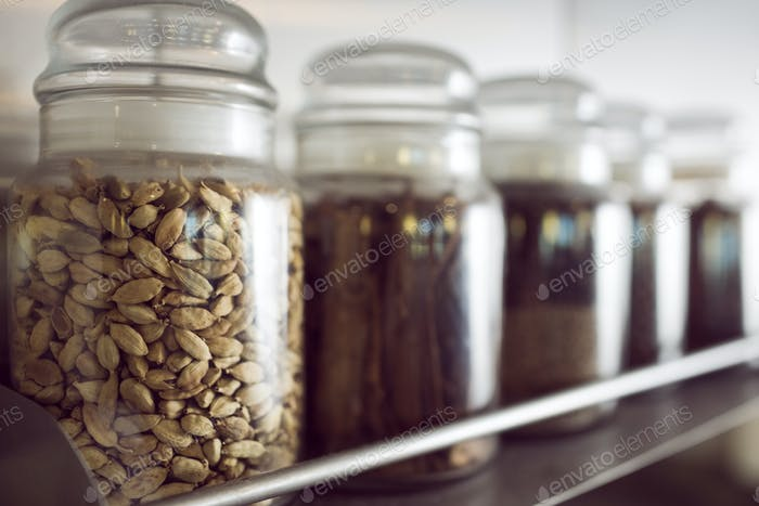 Closeup of assorted spices in bottles on shelf