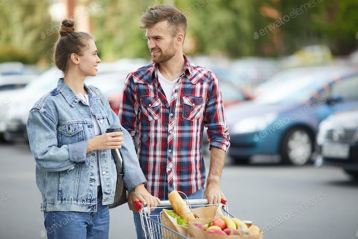 Couple with Shopping Cart in Parking Lot