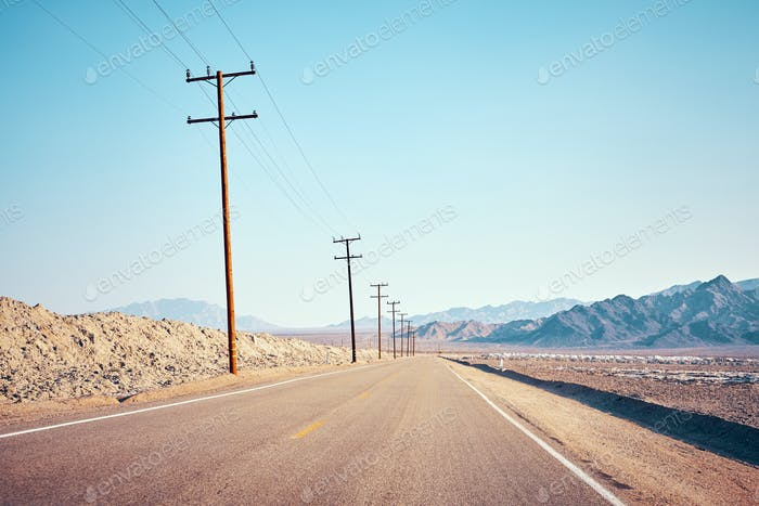 Desert road with wooden electricity posts.