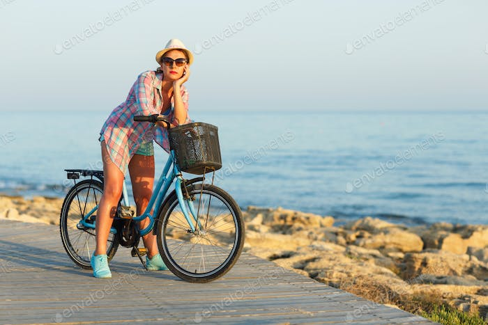 Carefree woman with bicycle riding on a wooden path at the sea