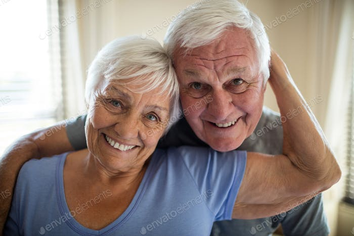 Portrait of senior couple embracing each other in the bedroom