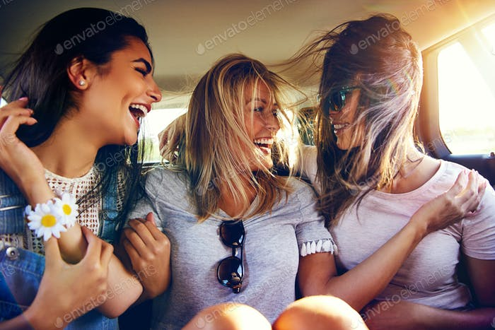 Three vivacious young women in the back of a car