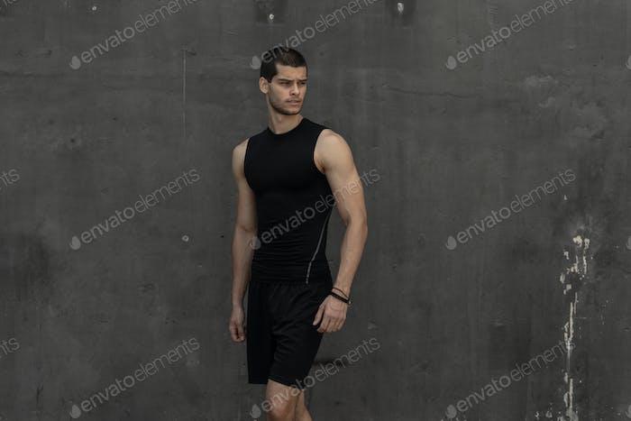 Sport model man posing gray wall background