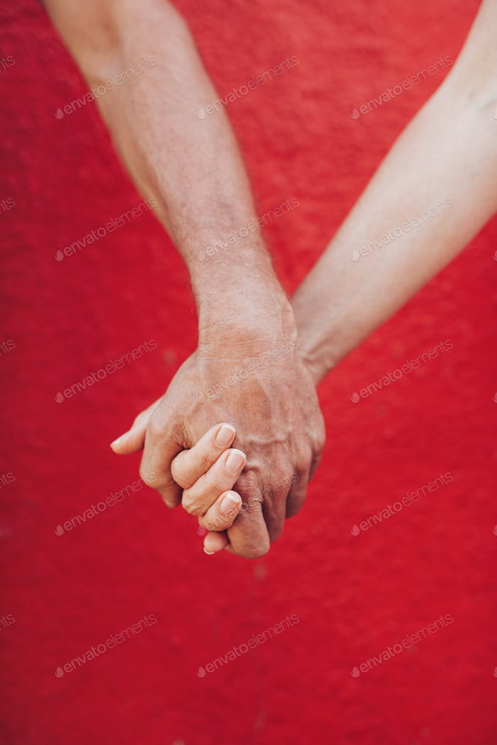 Loving man and woman holding hands