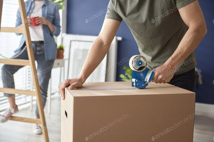 Hands of man using a adhesive tape for packing