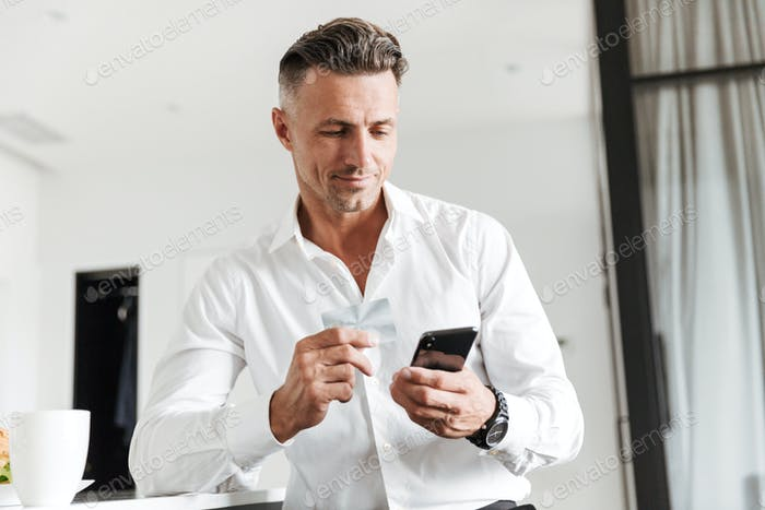 Smiling man dressed in formal clothes drinking coffee