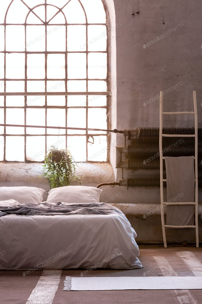 Ladder next to grey bed with pillows in bright loft interior wit