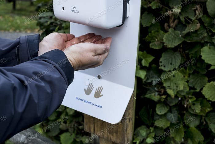 Close up of person using automatic hand sanitizer dispenser during Corona virus crisis.
