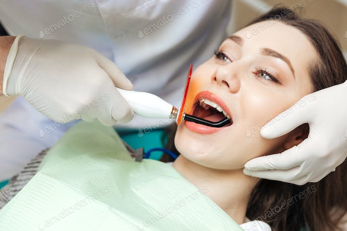 Close-up portrait of a girl getting her teeth bleached