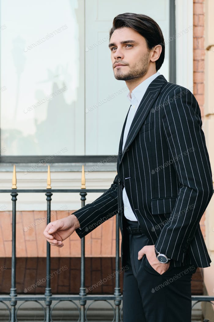 Young handsome stylish man in classic striped jacket dreamily looking aside standing on city street