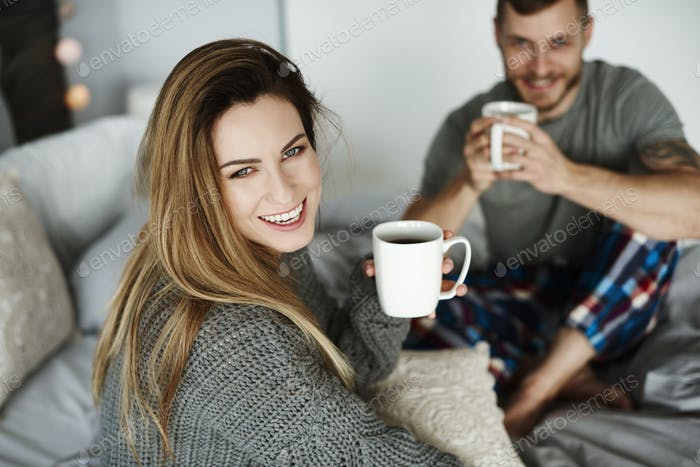 Heterosexual couple with coffee in bed