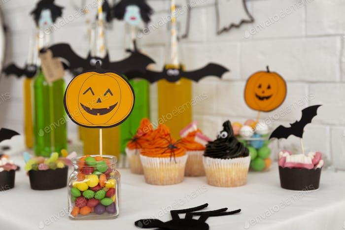 Lächelnd Halloween Kürbis schlägt süße Süßigkeiten und leichte Getränke