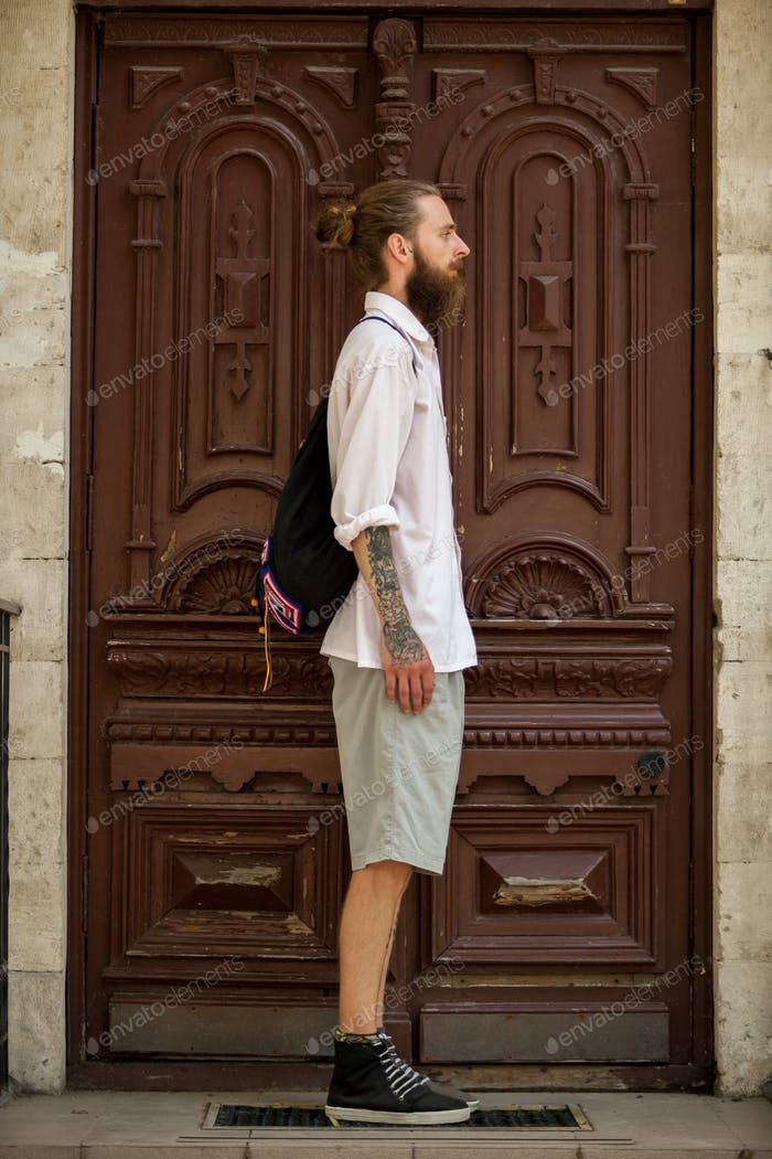 Hipster in white shirt posing in front of a door