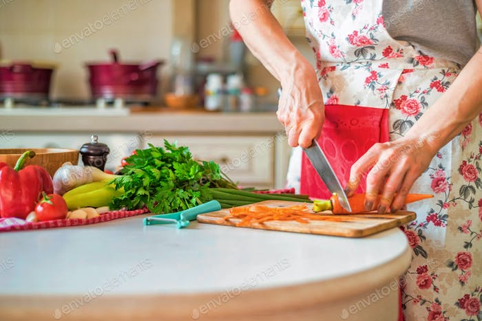 Female hand with knife cuts carrot in kitchen. Cooking vegetables