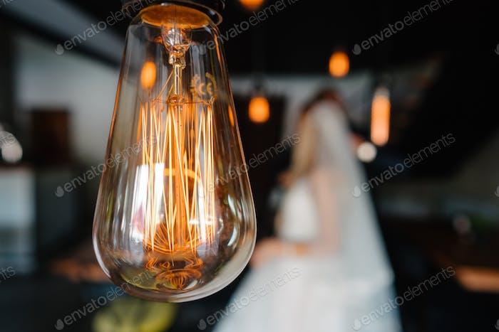 retro bulbs lights. newlyweds couple embracing