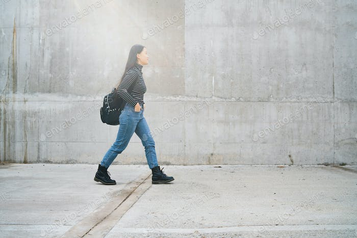Asian woman walking against grey wall.