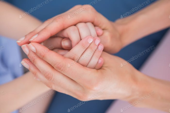Mother and daughter touching hands at home in the living room
