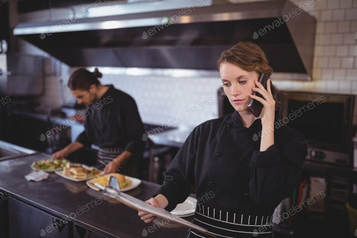 Young waitress talking on smartphone while waiter preparing food in commercial kitchen